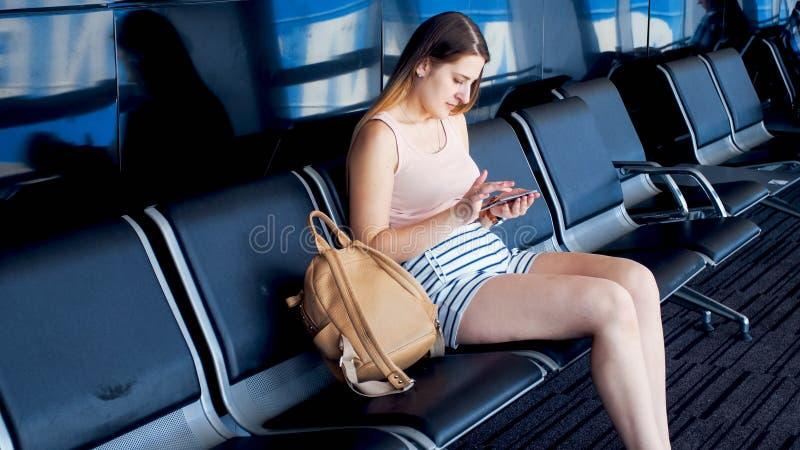 Piękny młodej kobiety obsiadanie w poczekalni przy lotniskowym terminal i używać smartphone obrazy royalty free