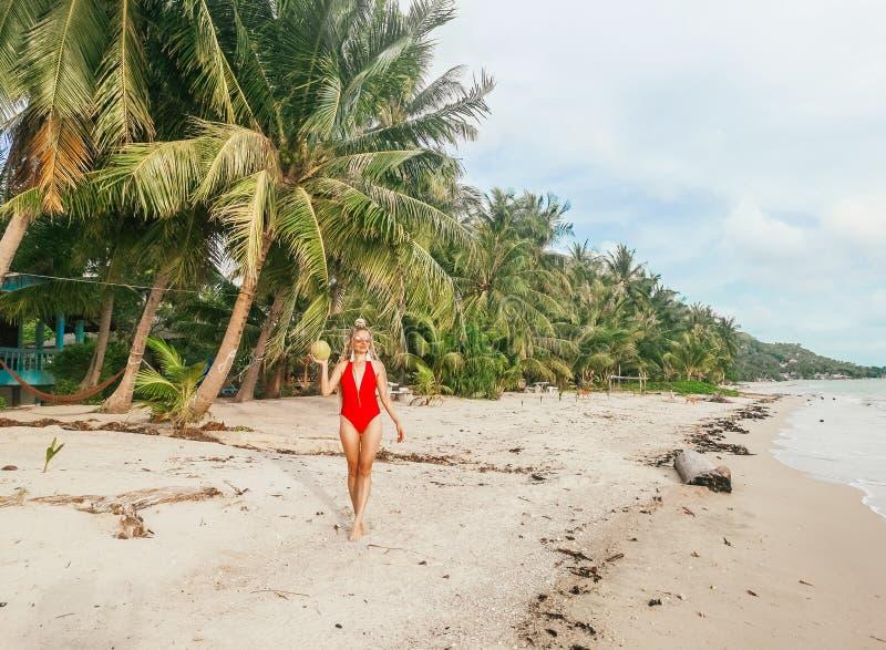 Piękny młodej kobiety odprowadzenie na plaży wzdłuż drzewek palmowych trzyma kokosowymi w Koh Phangan, Tajlandia obraz stock