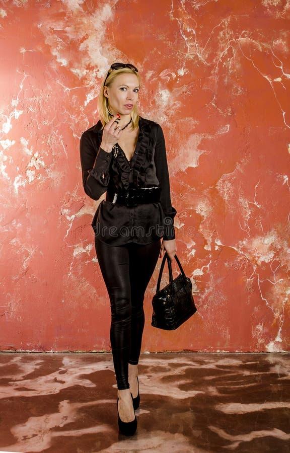 Piękny młodej kobiety odprowadzenie z torbą moda i w czarnej koszula i spodniach. zdjęcia royalty free