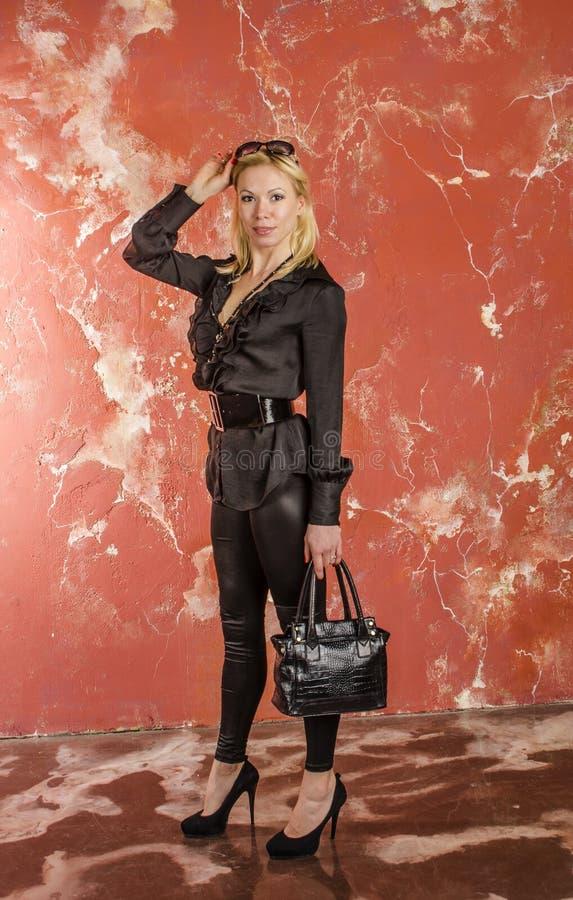 Piękny młodej kobiety odprowadzenie z torbą moda i w czarnej koszula i spodniach. zdjęcie royalty free