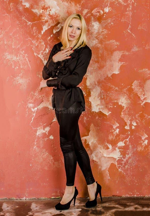 Piękny młodej kobiety odprowadzenie z torbą moda i w czarnej koszula i spodniach. zdjęcia stock