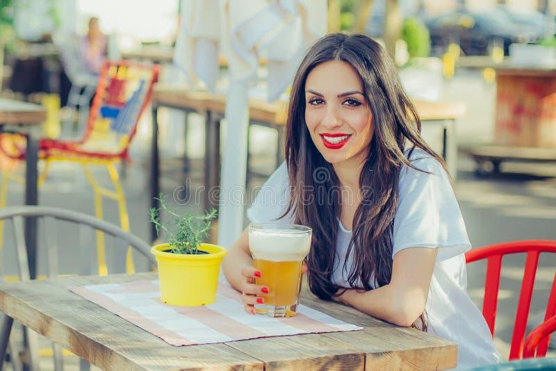 Piękny młodej kobiety pić piwny i cieszyć się letniego dzień zdjęcia stock