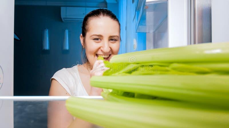 Piękny młodej kobiety powalać głodny przy nocy łasowania selerem na kuchni zdjęcia stock