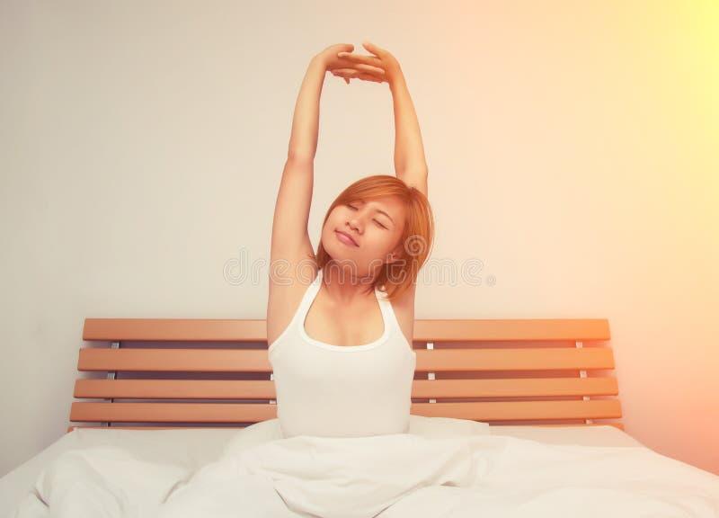 Piękny młodej kobiety rozciąganie na łóżku po budził się w mor zdjęcia royalty free