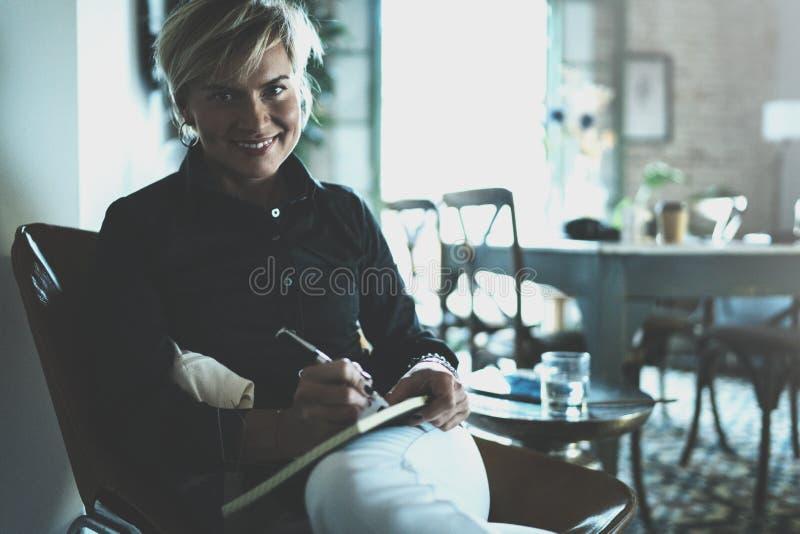 Piękny młodej kobiety writing coś w nutowym ochraniaczu podczas gdy siedzący na karle przy żywym pokojem Powabny żeński studiowan zdjęcie stock