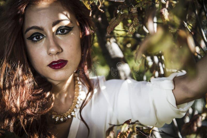 Piękny młodej kobiety zakończenie w białym pulowerze przeciw zieleni o, fotografia stock