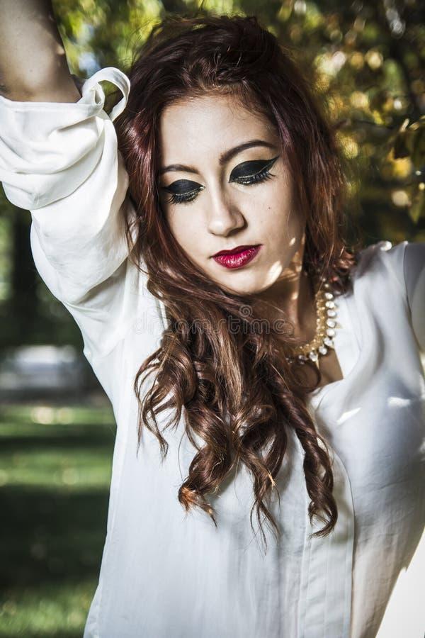 Piękny młodej kobiety zakończenie w białym pulowerze przeciw zieleni o, obraz royalty free