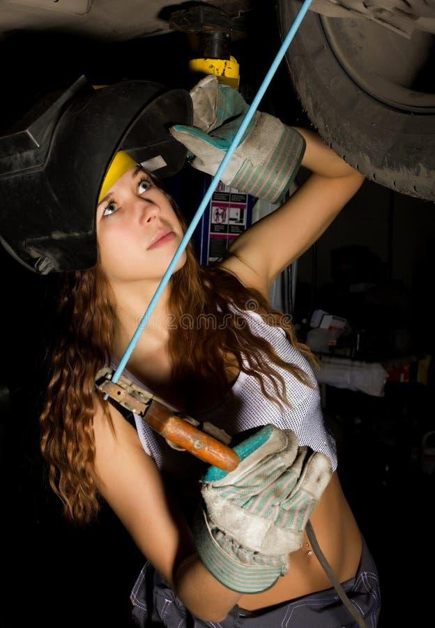 Piękny młody żeński mechanik sprawdza samochód w auto remontowym sklepie Dziewczyna spawacz przygotowywa łączyć części Seksowny fotografia royalty free