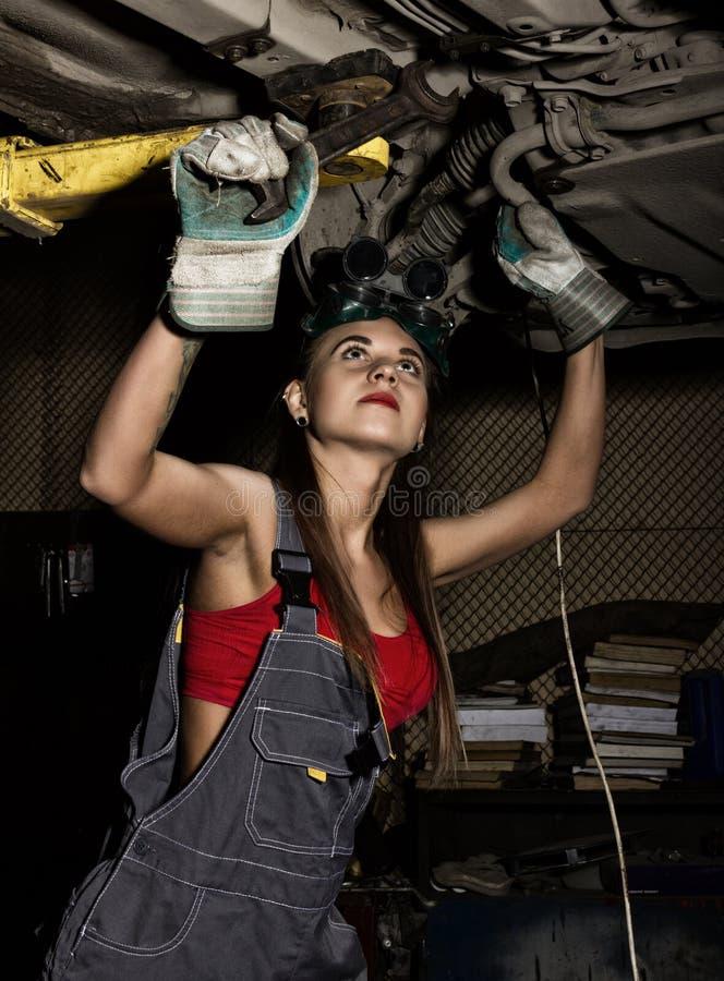 Piękny młody żeński mechanik sprawdza samochód w auto remontowym sklepie mechanik seksowny obrazy stock
