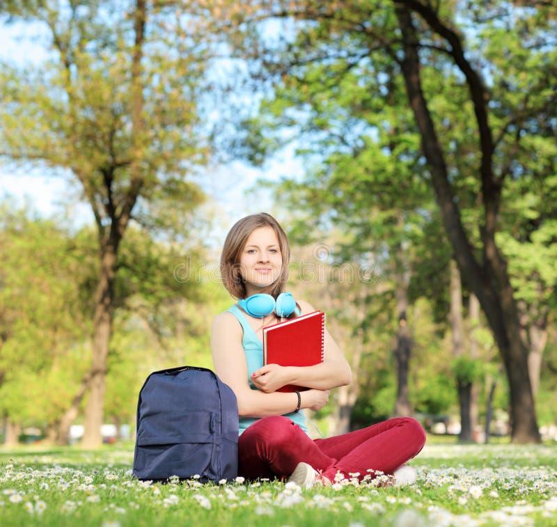 Piękny młody żeński uczeń z książki i hełmofonów siedzieć obrazy royalty free