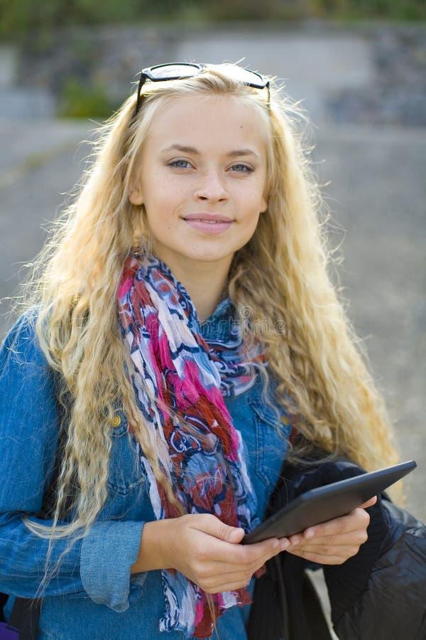 Piękny młody żeński uczeń z pastylką w rękach obraz stock