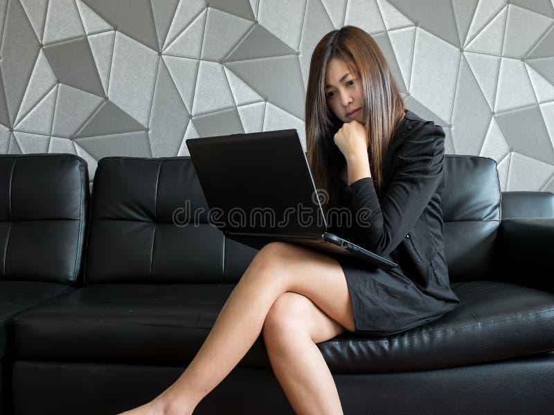 Piękny młody Asia biznesowej kobiety obsiadanie na kanapie, pracuje z laptopu i odzieży czerni kostiumu dopatrywania monitorem, p zdjęcia royalty free