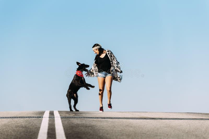 Piękny młody bawić się z jej psem obraz royalty free