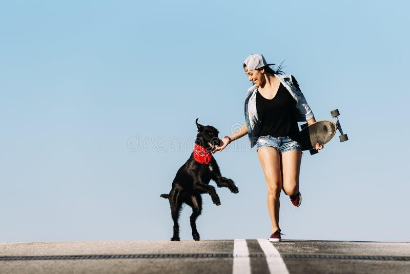 Piękny młody bawić się z jej psem obrazy stock