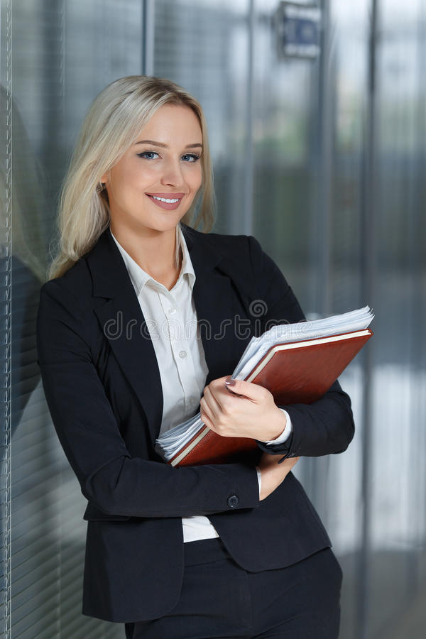 Piękny młody bizneswoman ono uśmiecha się i stoi z falcówką w biurze patrzeć kamerę fotografia royalty free