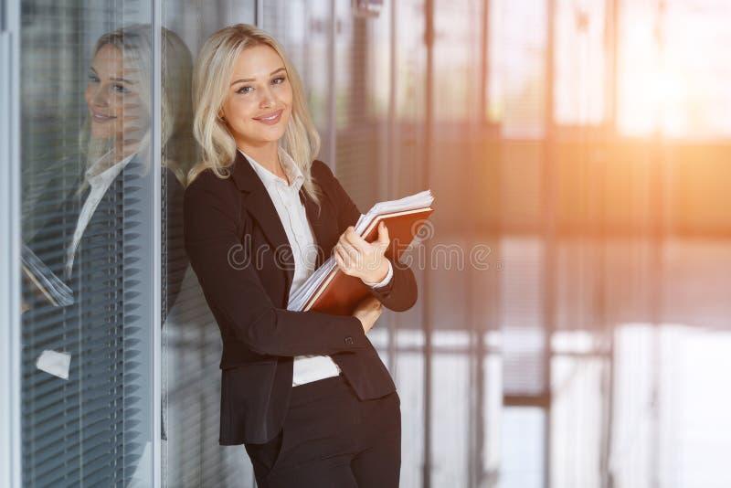 Piękny młody bizneswoman ono uśmiecha się i stoi z falcówką w biurze patrzeć kamerę kosmos kopii zdjęcie royalty free