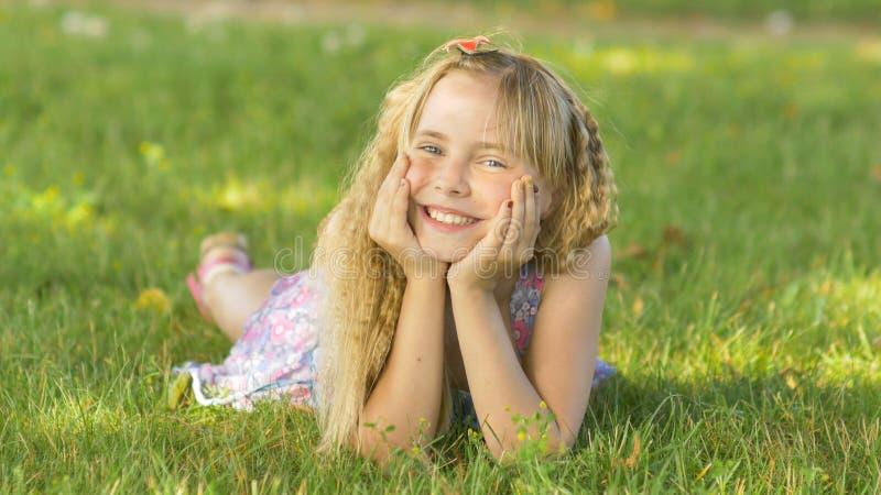 Piękny młody blondynki dziewczyny lying on the beach na polu, zielona trawa Outdoors Cieszy się naturę Zdrowy Uśmiechnięty dziewc fotografia stock