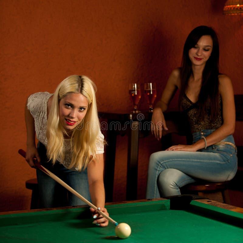 Piękny młody blondynki kobiety bawić się bilardowy w barze fotografia stock