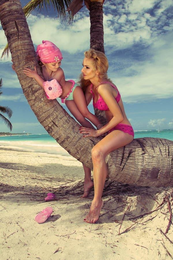 Piękny młody blondynki kobiety Mon obsiadanie na bagażniku drzewko palmowe z córką, małej dziewczynki princess obrazy stock