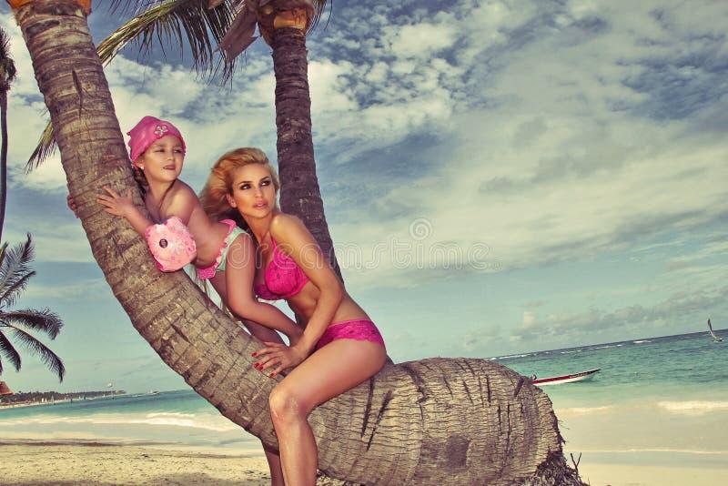 Piękny młody blondynki kobiety Mon obsiadanie na bagażniku drzewko palmowe z córką, małej dziewczynki princess zdjęcia stock