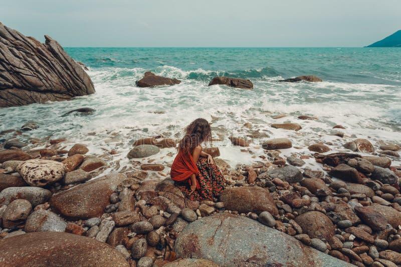 Piękny młody boho projektujący kobiety obsiadanie na kamiennej plaży fotografia stock