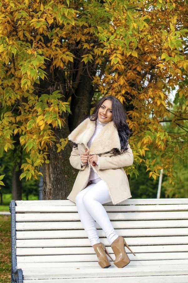 Piękny młody brunetki kobiety obsiadanie na ławce w jesieni zdjęcie royalty free