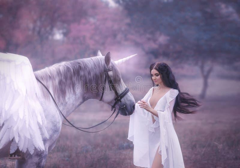 Piękny, młody elf, chodzi z jednorożec Jest ubranym nieprawdopodobnego światło, biel suknia Sztuki hotography zdjęcie royalty free