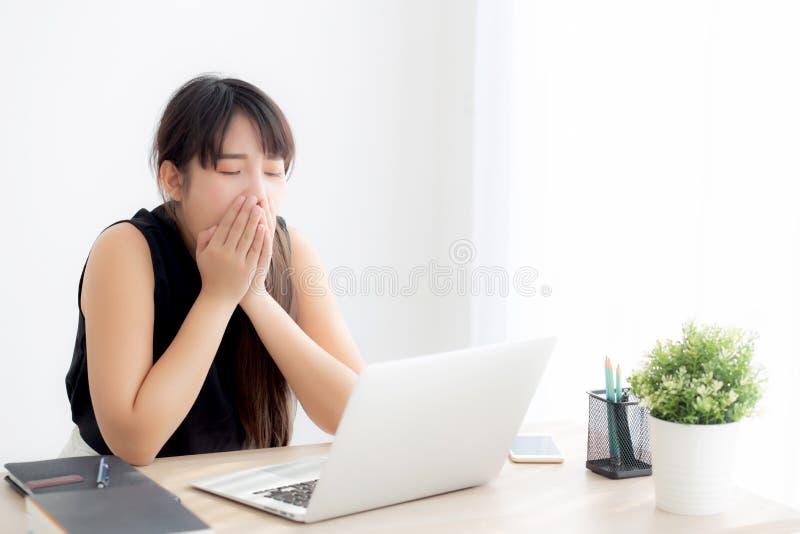 Piękny młody freelance azjatykci kobiety działanie zanudzający i męczący na laptopie przy biurem obraz royalty free