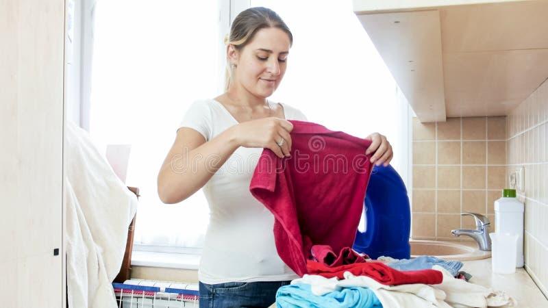 Piękny młody gospodyni domowej składać czysty odziewa w pralnianym pokoju zdjęcia stock