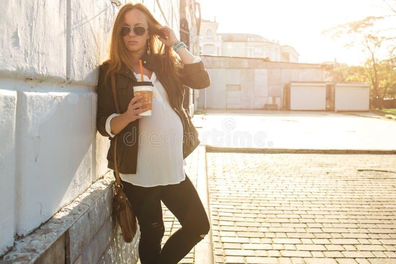Piękny młody kobieta w ciąży pić bierze oddaloną kawę obraz stock