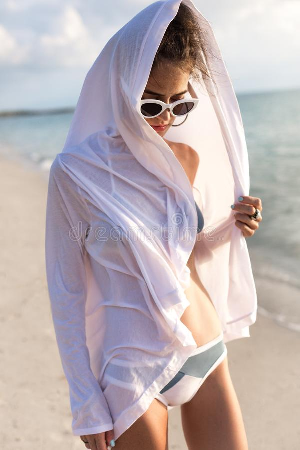 Piękny młody moda model w bikini z okularami przeciwsłonecznymi chodzi na plaży przy zmierzchem zdjęcia stock