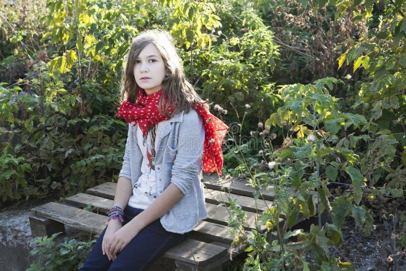 Piękny młody nastolatka obsiadanie na bagażniku drzewo obraz royalty free