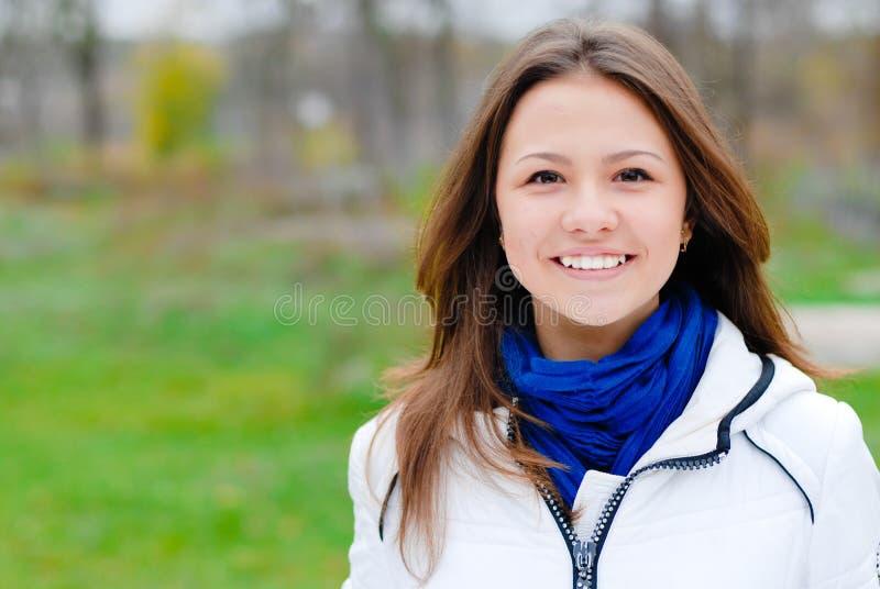Piękny młody nastoletni brunetki dziewczyny szczęśliwy ono uśmiecha się outdoors zdjęcia stock