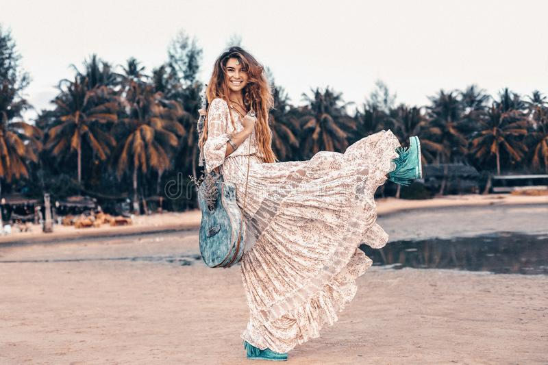 Piękny młody rozochocony moda model w biel sukni z gitarą ma zabawę przy zmierzchem outdoors zdjęcia stock