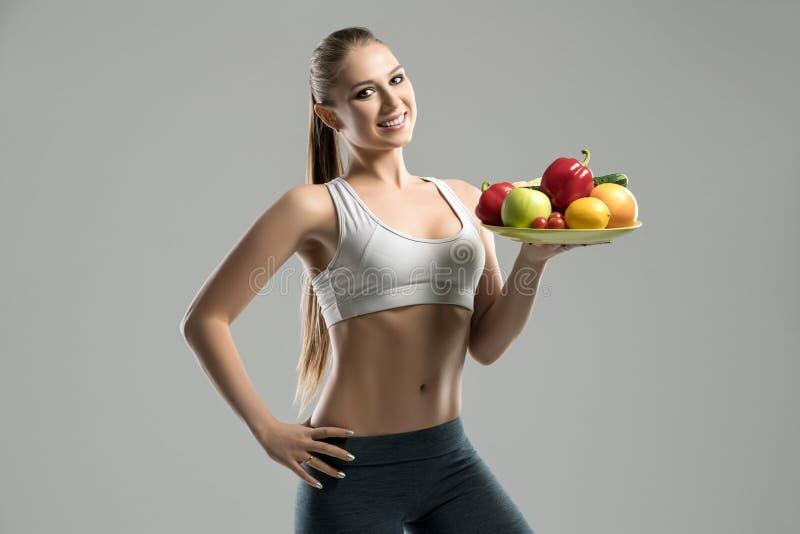 Piękny młody sportsmenki mienia talerz owoc zdjęcia royalty free