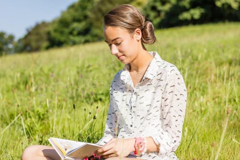Piękny młody studencki czytanie książka w parku obraz royalty free