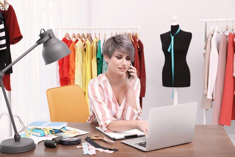 Piękny młody stylista opowiada na telefonie przy miejsce pracy fotografia royalty free
