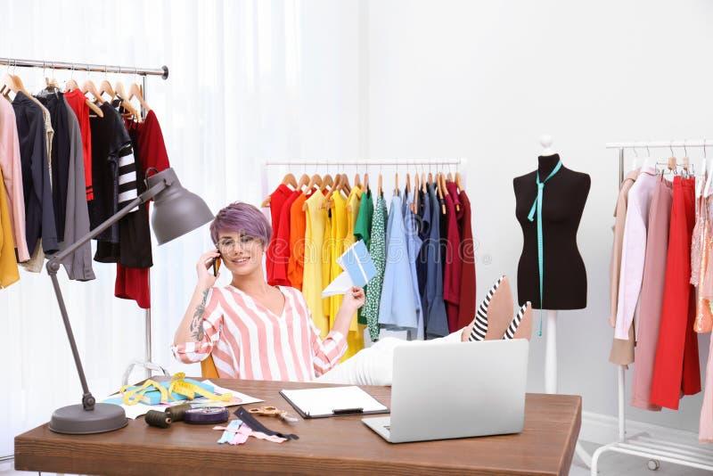 Piękny młody stylista opowiada na telefonie przy miejsce pracy pobliskim stojakiem zdjęcie royalty free