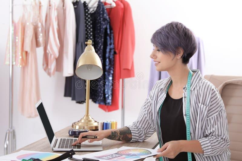 Piękny młody stylista pracuje z laptopem w studiu zdjęcie royalty free