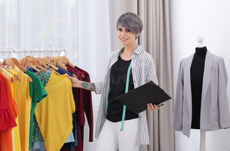 Piękny młody stylista z schowka wybierać odziewa obrazy royalty free