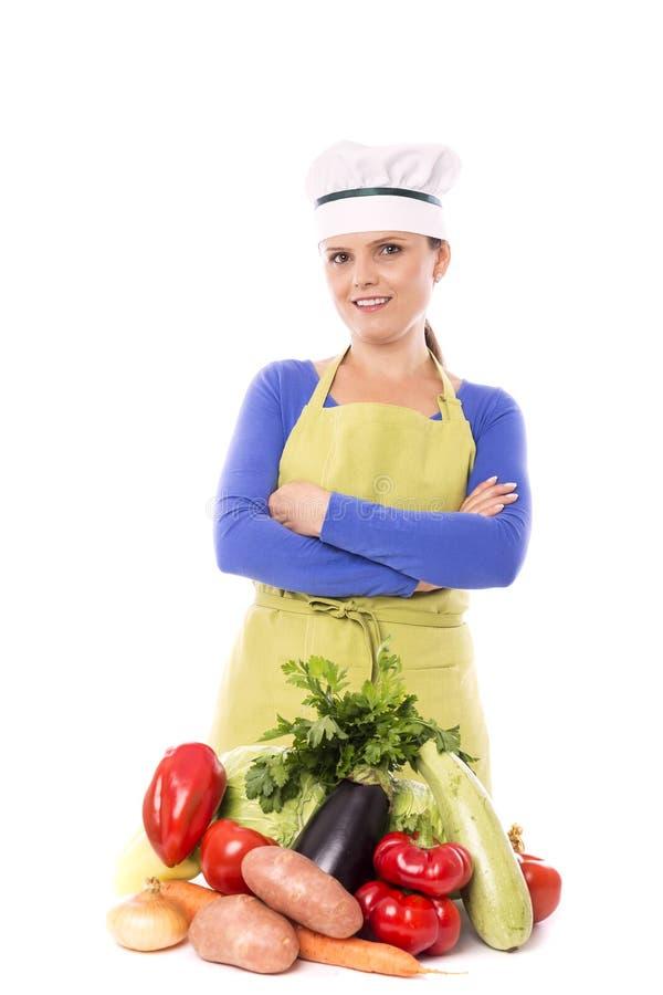 Piękny młody szef kuchni obok jej świeżych warzyw fotografia royalty free