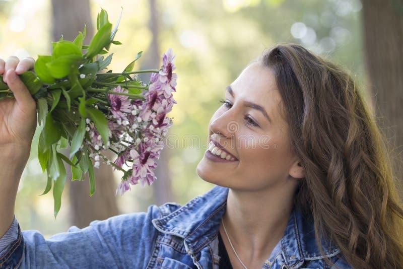 Piękny młody uśmiechnięty kobiety mienie kwitnie w jej ręce fotografia royalty free