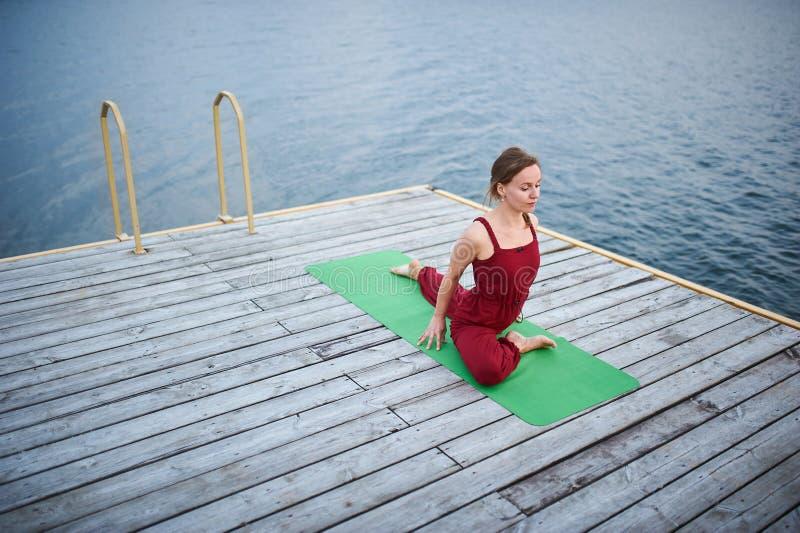 Piękny młodych kobiet praktyk joga asana Jeden Iść na piechotę królewiątko Gołębią pozę - Eka Pada Rajakapotasana na drewnianym p obrazy royalty free