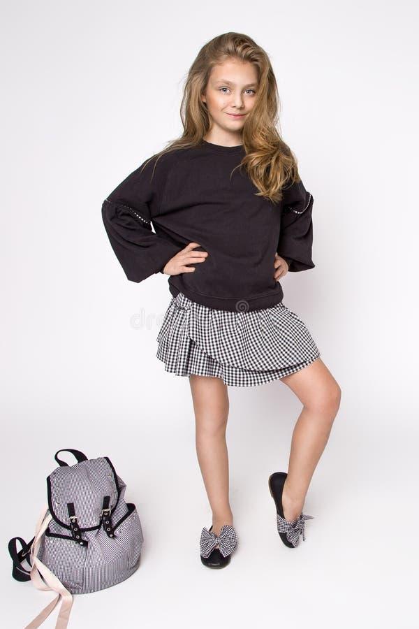 Piękny, mała dziewczynka ubierał w szkół ubraniach i szkolnym plecaku, pozy w studiu tylna szkoły fotografia royalty free