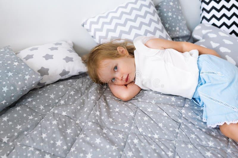 Piękny małej dziewczynki lying on the beach na łóżku wśród poduszek w jej sypialni fotografia stock