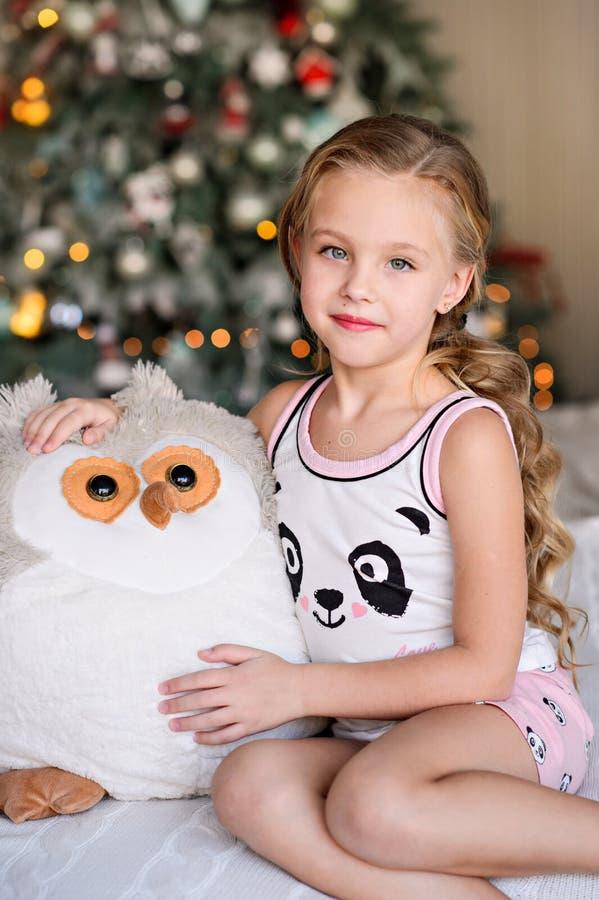 Piękny małej dziewczynki obsiadanie blisko choinki fotografia stock