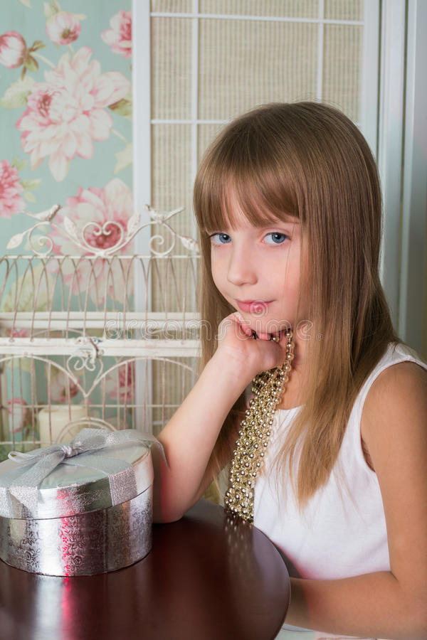 Piękny małej dziewczynki obsiadanie przy stołem z koraliki fotografia royalty free