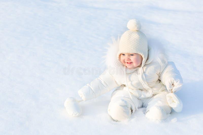 Piękny mały dziewczynki obsiadanie w białym śniegu obrazy royalty free