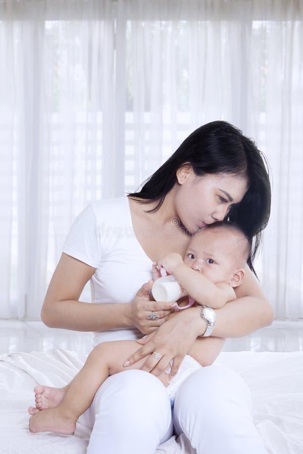 Piękny macierzysty całowanie jej dziecko w domu fotografia royalty free