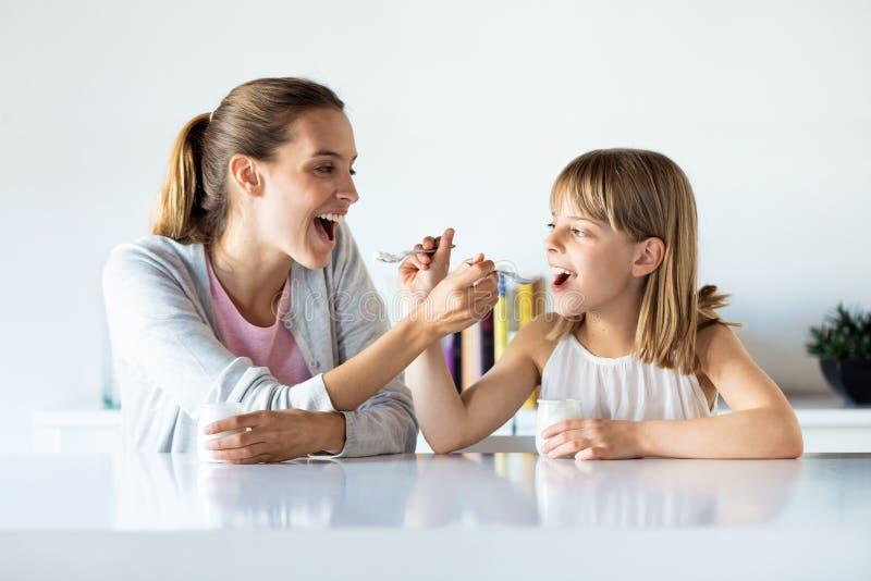 Pi?kny matki i c?rki ?ywieniowy jogurt do siebie w domu zdjęcia stock